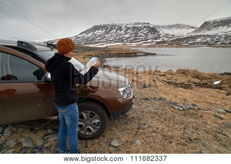 Woman traveler steps out of 4x4 rental car on holiday and looks at map, solo adventure roadtrip holiday