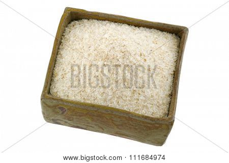 A squared clay bowl full of dried psyllium husk fiber to relieve constipation, irritable bowel syndrome, isolated on white