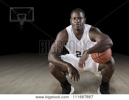 African American basketball Player holding a ball and posing in a darkened basketball arena.