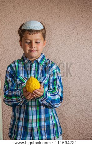 Etrog -  ritual fruit for the Jewish holiday of Sukkot. Beautiful seven year old boy in white knitted skullcap is holding citrus