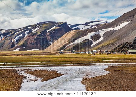 The picturesque valley in the national park Landmannalaugar, Iceland. Summer flood of meltwater flooded the road to tourist camping