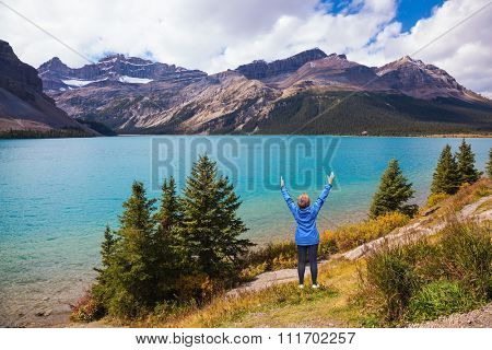 Bow Lake in Banff National Park, Canada. Middle-aged woman in blue jacket in awe of the beautiful nature threw up her hands
