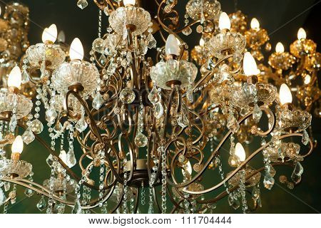 Beautiful vintage crystal chandelier in a room, Golden tones.