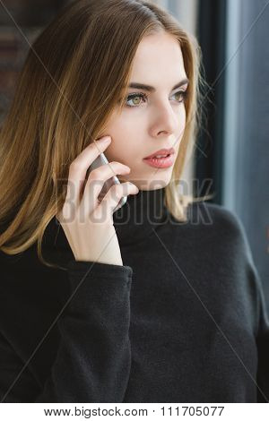Attractive serene young lady in black sweetshirt talking on mobile phone