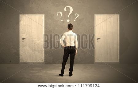 Salesman standing in front of two doors, unable to make the right decision concept with question marks above his head