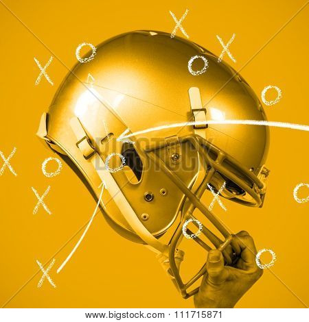American football player handing his sliver helmet against yellow background with vignette