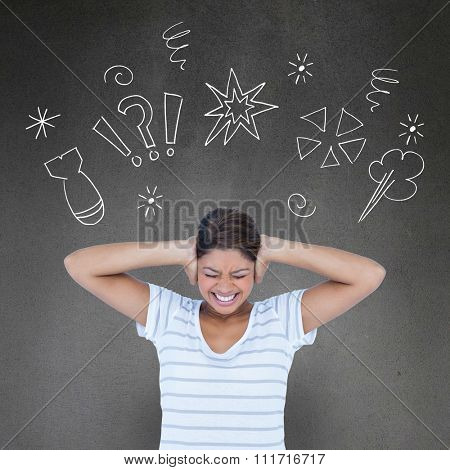Angry woman covering ears against grey room