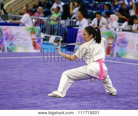 JAKARTA, INDONESIA - NOVEMBER 17, 2015: Emily Fan of the USA performs the movements in the women's Jianshu event at the 13th World Wushu Championship 2015 in Istora Senayan Stadium.