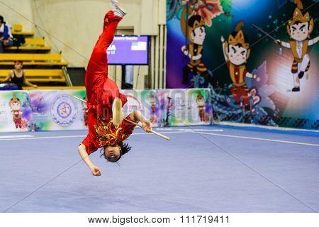 JAKARTA, INDONESIA - NOVEMBER 17, 2015: Ami Li of the USA performs the movements in the women's Gunshu event at the 13th World Wushu Championship 2015 in Istora Senayan Stadium.