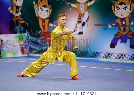 JAKARTA, INDONESIA - NOVEMBER 17, 2015: Justin Benedik of the USa performs the movements in the men's Compulsory Changquan event at the 13th World Wushu Championship 2015 in Istora Senayan Stadium.