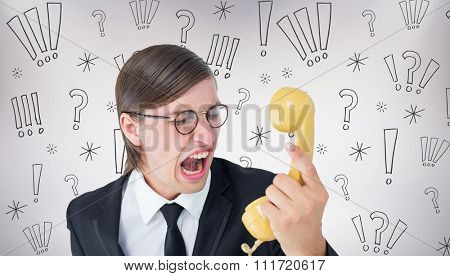 Geeky businessman shouting at retro phone against grey background