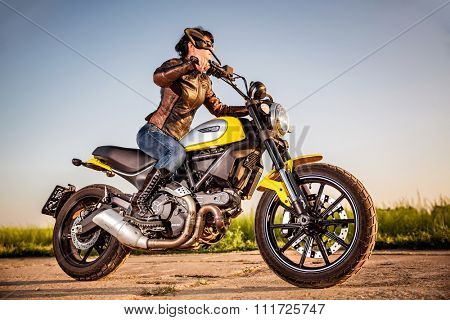 RUSSIA-AUGUST 11, 2015:Biker girl on a Scrambler Icon Ducati. A new Scrambler was introduced at the 2014 Intermot motorcycle show.Ducati is an Italian company that designs and manufactures motorcycles