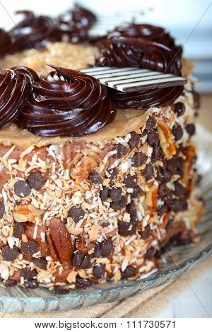 Closeup of a whole German Chocolate Cake with plates