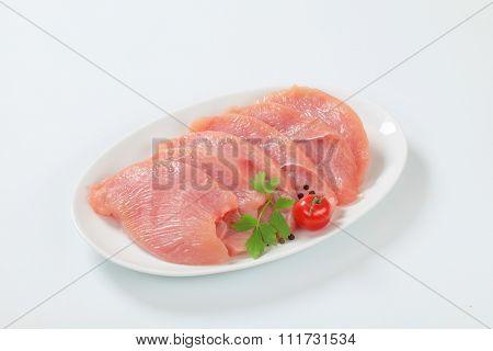 Raw turkey breast escalopes on plate