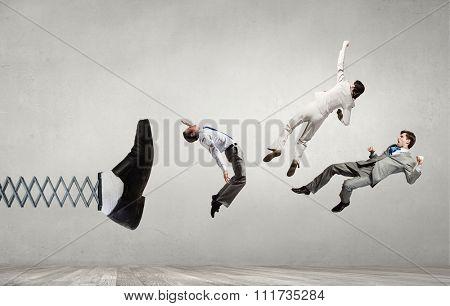 Big businessman foot on spring kicking business people