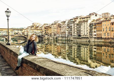 Beautiful young woman posing in front of amazing bridge Ponte Vecchio Florence Tuscany Italy. Travel destination. Cradle of the renaissance. poster