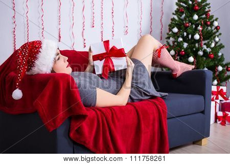 Chrstmas Concept - Happy Young Woman In Santa Hat With Gift Box Near Christmas Tree
