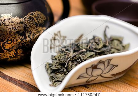 Dry green tea on wooden background