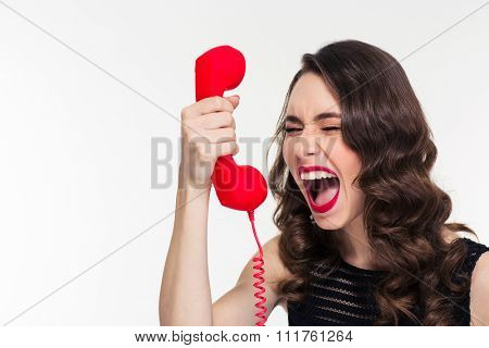 Desperate stressed curly young woman with retro hairstyle screaming in red telephone receiver over white background