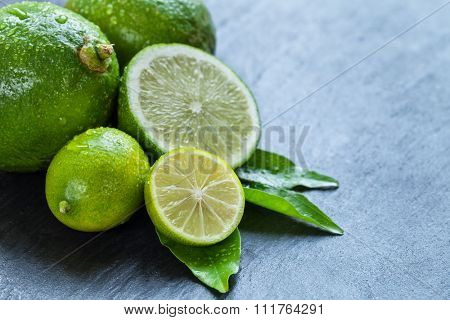 Fresh dewy limes place on black stone, copyspace for text