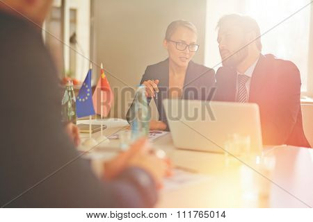 Young woman interpreting speech of partner to businessman at international conference