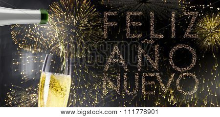 Champagne pouring against glittering feliz ano nuevo
