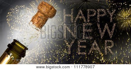 Close up of champagne cork popping against glittering happy new year