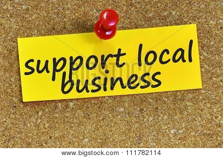 support local business word on yellow notepaper with cork background. poster