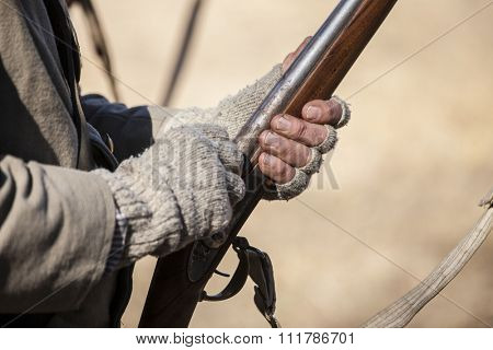 Hands of man in vintage clothing holding muzzle loading rifle
