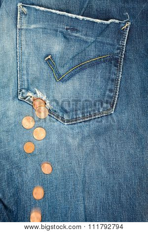 Coins fall out from a hole in jeans pocket