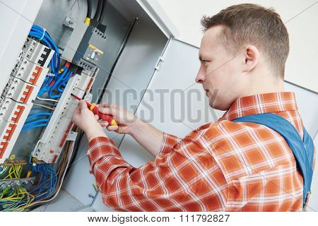 electrician with screwdriver fixing high voltage switching electric actuator in fuse box