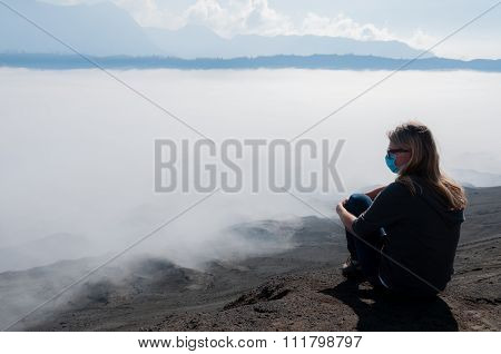 Blond woman Resting at The Mountain Top watching fog mist and smoke