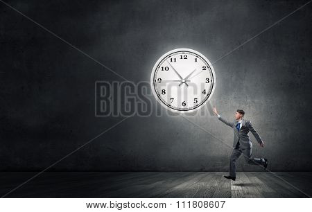 Businessman running and trying to catch time