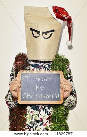 a young man dressing casual wear with a paper bag in his head and a santa hat in the top and some tinsel in his shoulders shows a chalkboard with the text I dont like christmas
