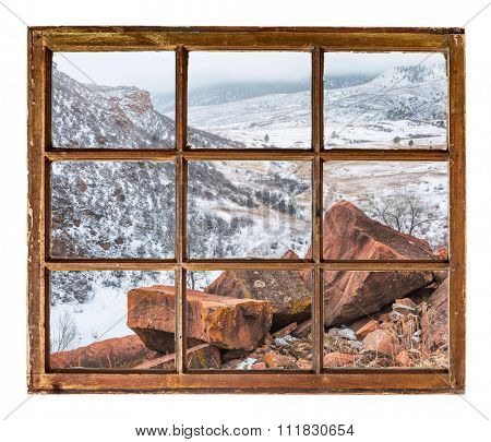 sandstone rocks and a mountain valley in fog and snow  as seen  through vintage, grunge, sash window with dirty glass - travel or vacation concept