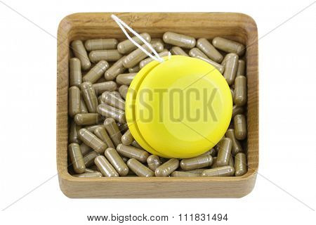A wooden box full of herbal medicines with yellow YoYo, isolated on white represent the idea of Yo-Yo dieting Effect