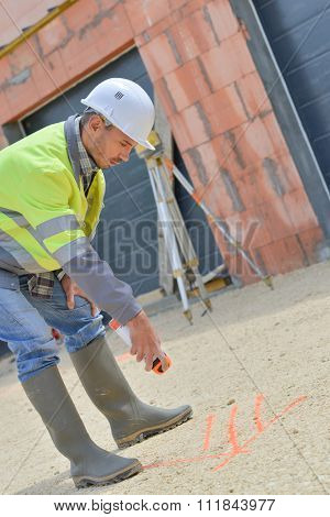 Workman spraying arrow on to ground