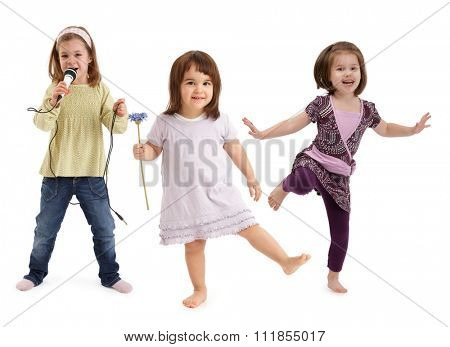 Three cute little girls dancing, singing to microphone, having fun over white background.