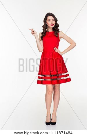 Full length portrait of a happy woman in red dress pointing finger away isolated on a white background