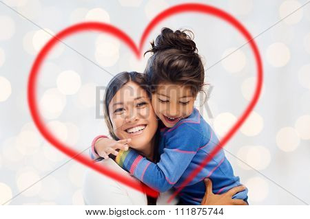 family, children, love and happy people concept - happy mother and daughter hugging over holidays lights background and red heart shape