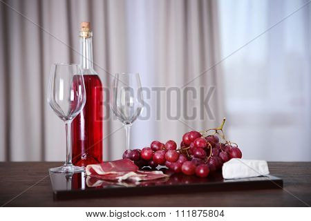 Pink wine bottle, two wineglasses, grape, slices of bacon and cheese on a table, still life