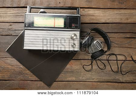 Radio with headphones and microphone on wooden background