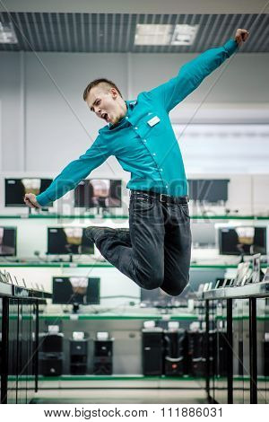 Happy manager jumping in the electronic shop