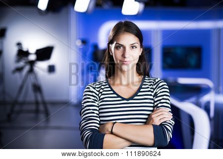 Young beautiful brunette television announcer at studio during live broadcasting.Female TV director
