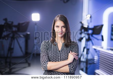 Young beautiful brunette television announcer at studio standing next to the camera.