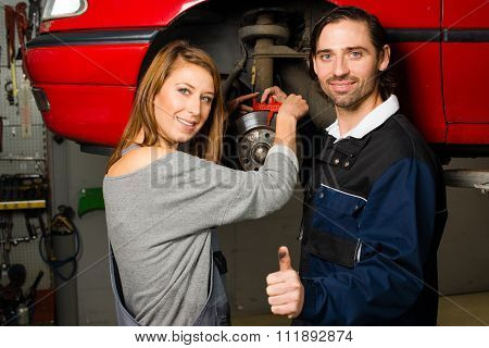 Auto mechanic and female trainee in garage