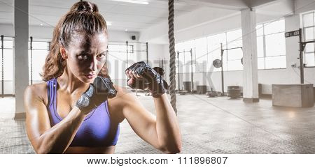 Portrait of female confident boxer with fighting stance against exercise ropes hanging and equipment