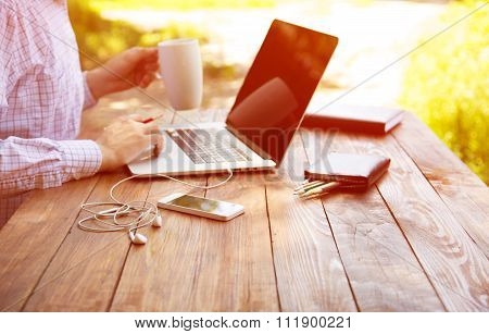 Escaped of office man sitting at natural country style wooden desk with electronic gadgets