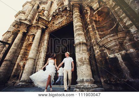 Happy wedding couple walking in old city