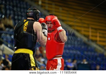 JAKARTA, INDONESIA - NOVEMBER 18, 2015: Bagdat Kenzhetayev of Kazakhstan (red) fights Muslim Salikhov of Russia (black) in the men's 80kg Sanda event at the 13th World Wushu Championship 2015.